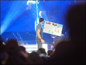 Singer Luke Bryan with a sign given to him by a member of the audience.