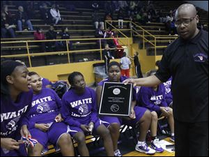 Waite head coach Manny May shows his players the 2nd place plaque after the game.