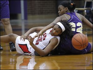 Rogers' Akienreh Johnson and Waite's Janae Kenny scramble for a loose ball during the second half.