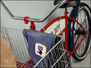 A letter carrier jacket rests on a bicycle.