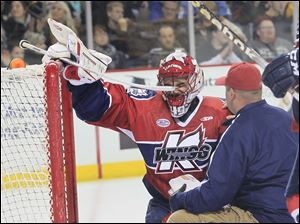 K-Wings' goalie Joel Martin gets some medical attention in the first period.