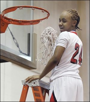 Cha'Ron Sweeney, who scored 20 points, cuts down the net after Rogers defeated Waite to win the City League girls basketball championship for the second straight year.