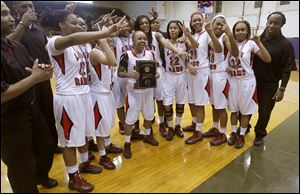 Cha'Ron Sweeney holds the City League girls basketball championship plaque as the team celebrates. The Rams are 19-3.