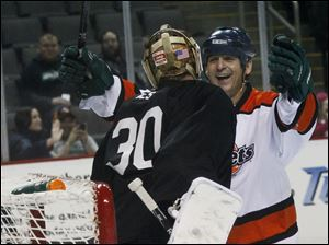 Toledo goaltender Doug Teskey is embraced by Fort Wayne's Adam Lewis during the third period.