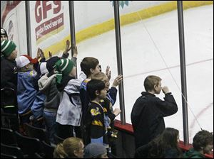 Young fans pound on the glass during the third period of the alumni game.