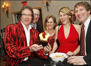 International magic champion Pattrick Przysiecki, left, entertains guests with his flaming wallet, from left, Ray and Joyce Miller, Melanie Miller, and Kevin Rantanen.