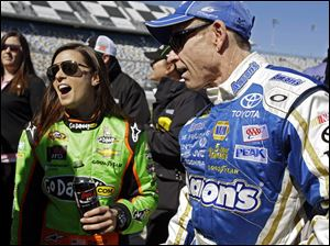 Mark Martin, right, and Danica Patrick laugh on pit road after their qualifying runs for the NASCAR Daytona 500 Sprint Cup Series auto race at Daytona International Speedway, in Daytona Beach, Fla. Patrick won the pole, becoming the first woman to secure the top spot for any Sprint Cup race.