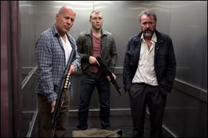 Bruce Willis as John McClane, left, Jai Courtney as his son Jack, center and Sebastian Koch as Komarov in a scene from