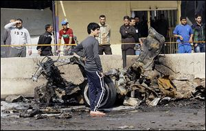 Iraqis inspect the scene of a car bomb attack in Baghdad on Sunday. A series of car bombs exploded within minutes of each other as Iraqis were out shopping.