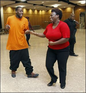 Ramar Jones dances with Ebony High during an urban dance and ballroom workshop at the University of Toledo's Student Union Ingman Room. Calling the instructions is Edwin Rhodes.