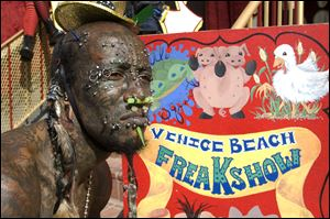 Creature, of AMC's new reality show 'Freakshow,' waits for passersby to come see the Venice Beach Freakshow on the boardwalk of Venice Beach, Calif.