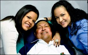 Venezuela's President Hugo Chavez, center, poses for a photo with his daughters, Maria Gabriela, left, and Rosa Virginia at an unknown location in Havana, Cuba, Thursday.