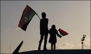 Libyan children wave national flags as they look out over Tahrir Square in Benghazi during a celebration. People used fireworks and sent balloons in the sky.