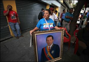 A woman holds a painting of President Hugo Chavez as supporters gather around Bolivar square after his return to the country in Caracas, Venezuela today.