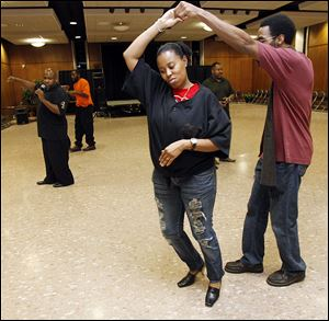 Tanisha Elliott, 33, of Fancy Footwork, dances with Rineil Rayford during an urban dance and ballroom workshop at UT's Student Union Ingman Room.
