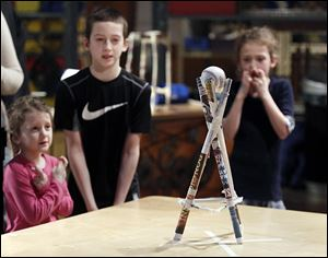 Sylvania siblings Chloe, 4, Jadon, 10 and Caelyn, 7, Thompson keep their fingers crossed, hoping their ball on top of their paper tower won't be blown off by a large fan. The Thompsons participated in the Paper Tower Engineering Challenge at the Imagination Station in Toledo on Monday.
