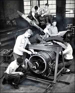 Students and their instructor work on a Westinghouse J-34 Turbo Jet engine at Macomber.  During World War II, Macomber focused on defense and opera
