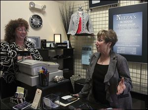 Elizabeth Leis, left, and Karen Barrington, owners of Nitza's, a clothing shop in Lima, Ohio, talk about Ohio Gov. John Kasich's State of the State address being given in their city.