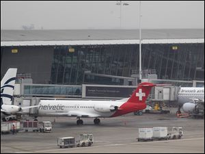 Baggage carts make their way past a Helvetic Airways aircraft at Brussels Airport where thieves stole millions' of dollars worth of diamonds from the hold of a Swiss-bound plane without firing a shot, authorities said.