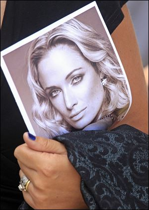 A woman holds a photo of Reeva Steenkamp, as she leaves her funeral in Port Elizabeth, South Africa, today.