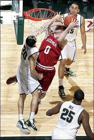 Indiana's Will Sheehey shoots over Michigan State's Travis Trice (20) as Derrick Nix (25) and Denzel Valentine watch during the first half on Tuesday.