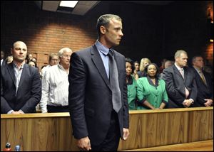 Olympian Oscar Pistorius stands following his bail hearing in Pretoria, South Africa, today. He is charged with premeditated murder.