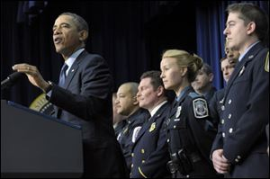 President Obama, accompanied by first responders behind him, gestures as he speaks in Washington today.