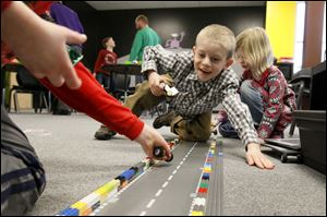 Grayson Scheub, 6, center, cheers as he pits his Lego car against another child's during a demolition derby during recent class at Build It in Perrysburg.