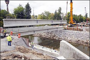 Workers install beams for a bridge on Perrysburg-Holland Road in Toledo. A higher state gas tax could accelerate road construction and repair.