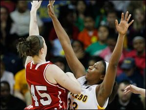 Northern Illinois' McKenzie Hoelmenn shoots over Toledo's Yolanda Richardson during the first half.