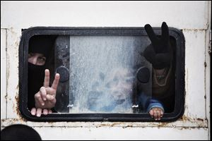 Displaced Syrian people make the victory sign inside wagon while going to Azaz camp for displaced people today, north of Aleppo province, Syria.