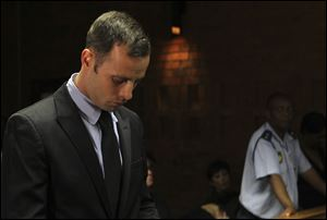 Olympic athlete Oscar Pistorius stands inside the court as a police officer looks on during his bail hearing at the magistrate court in Pretoria, South Africa, today.