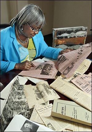 Linnie Willis, executive director of the Lucas Metropolitan Housing Authority, looks at an old newspaper article from a time capsule that was found during the demolition of the Brand Whitlock Homes in Toledo. The copper capsule was found in the summer.