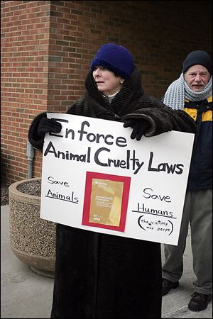Mary Ellen Coleman of Findlay urges enforce-ment of animal cruelty laws outside Findlay Municipal Court.