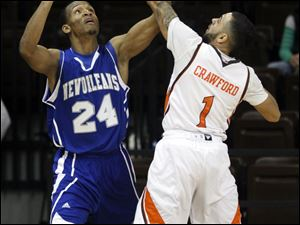 Bowling Green State University player Jordon Crawford, 1, knocks the ball away from University of New Orleans player Maurice County, 24.