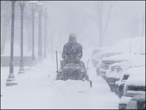 A man clears snow from the sidewalks around Friends University in Wichita, Kan. as heavy snow falls Wednesday morning.