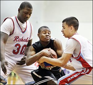 Bowsher's Mark Washington, left, and Cameron White, right, defend Start's Dion Ivery during the City League championship game Thursday. Ivery scored 10 of his 17 points in the second half.