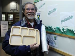 Sylvania Senior Center member Mon Taroy holds an eco-friendly lunch tray and a stack of cups.