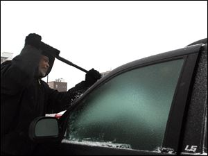 Jock Williams scrapes ice off of his windshield today. Heavy snow and wind slowed traffic and closed schools.