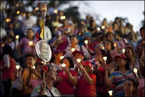 People hold up candles and images of Venezuela's President Hugo Chavez during candlelight vigil to pray for his health as he remains in a hospital undergoing cancer treatment, today in Caracas, Venezuela.