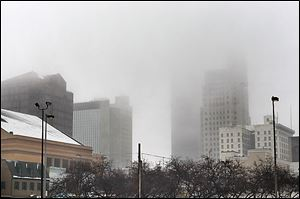 Fog envelops downtown Toledo. After snowfall overnight, temperatures hovered in the low to mid-30s much of the day.