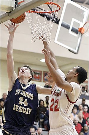 Parker Ernsthausen of St. John's shoots against Central Catholic's Nate Harris.