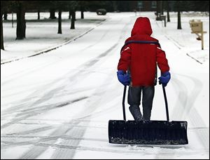 Toledoan Augustine Rancatore, 11, carries a big shovel as he walks to homes in South Toledo, selling his services of removing snow and ice from driveways and walks. Most schools were closed Friday.
