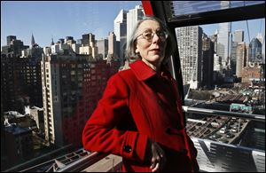 Janet Falk, a public relations professional, rides a tramway with a Manhattan view behind her on Thursday. Ms. Falk applied for a job at a New York City law firm two years ago, but the recruiter told her she wouldn't be considered because she had been out of work for more than 3 months.