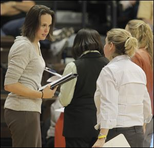 Assistant coach Ali Mann, left, speaks with head coach Jennifer Roos during a time out ealier this season.
