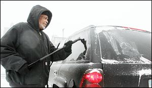 Jock Williams scrapes ice off of his windshield downtown. A thin but stubborn layer coated many vehicles. But it was the first time in weeks that many local drivers needed to spend much time scraping ice.