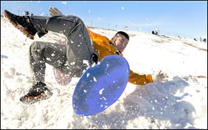 Miguel Sanchez, 16, flies off his sled as he goes off a ramp of snow today while sledding with friends in Garden City, Kan.