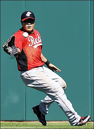 The Reds' Shin-Soo Choo fields a hit by the Indians' Carlos Santana in the first inning.
