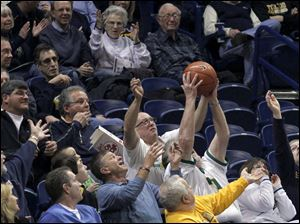 Fans reach for a ball wildly overthrown by McNeese State.