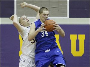 Anthony Wayne's Mark Donnal pulls down a rebound in front of Maumee's Sam Kamer.